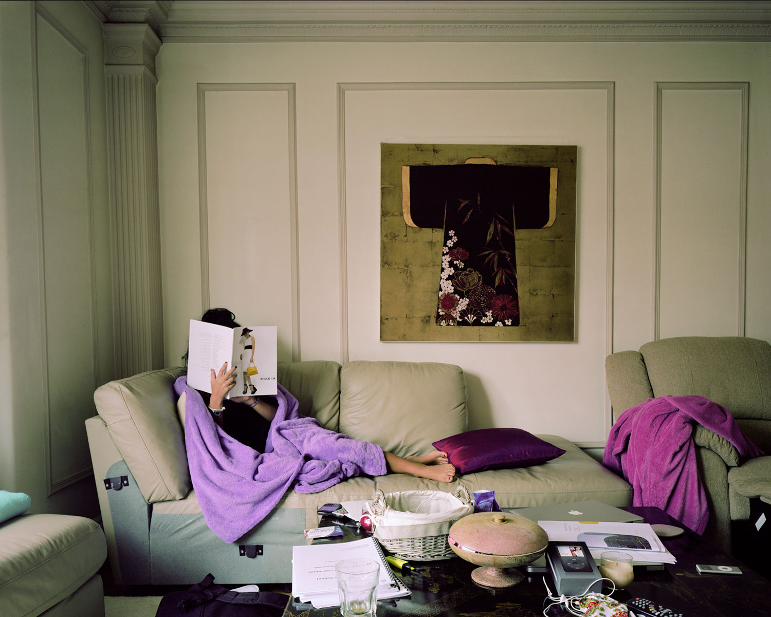 A woman, face obscured, reading a magazine reclining on a sofa