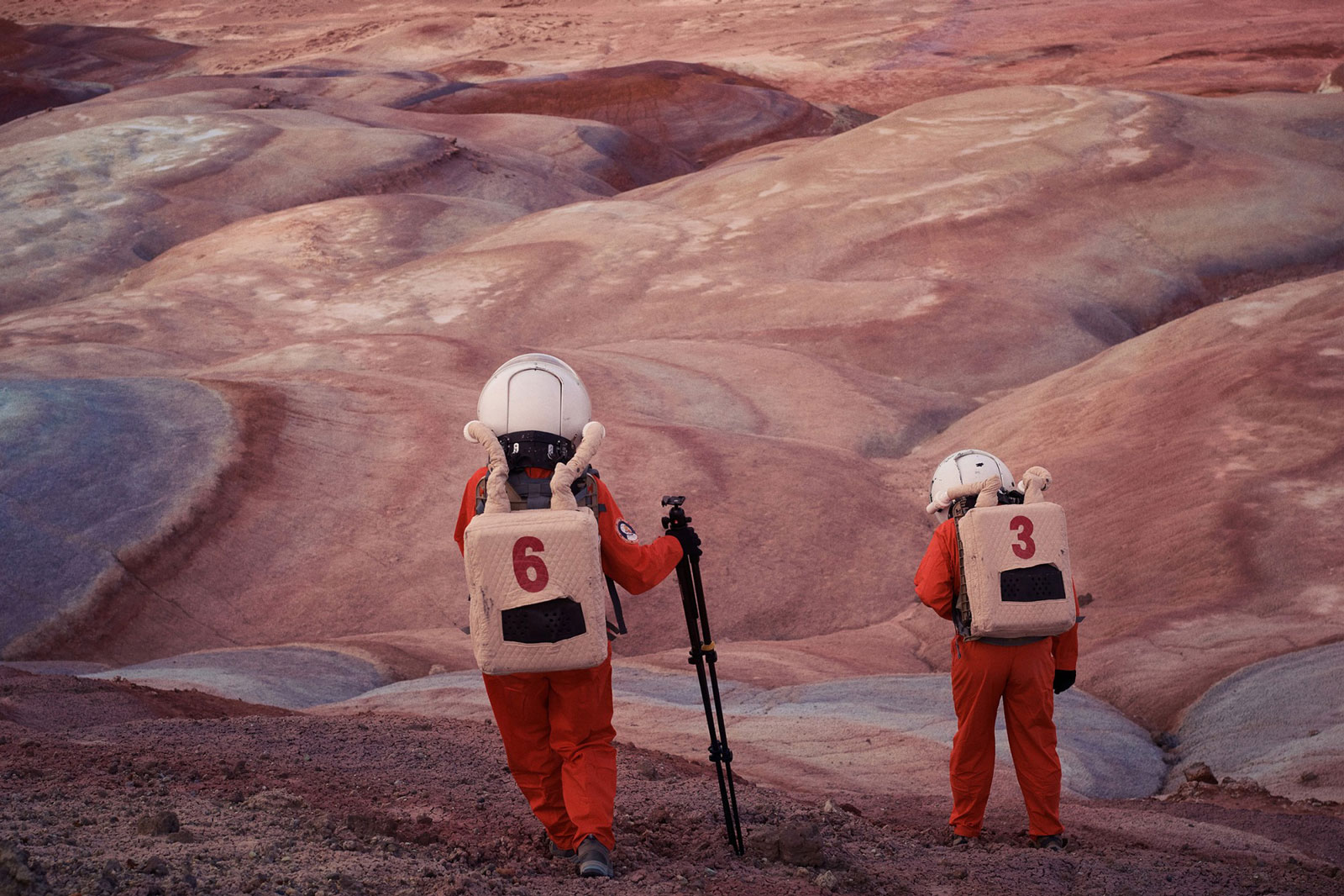 two astronauts step out into a surreal mars-like landscape