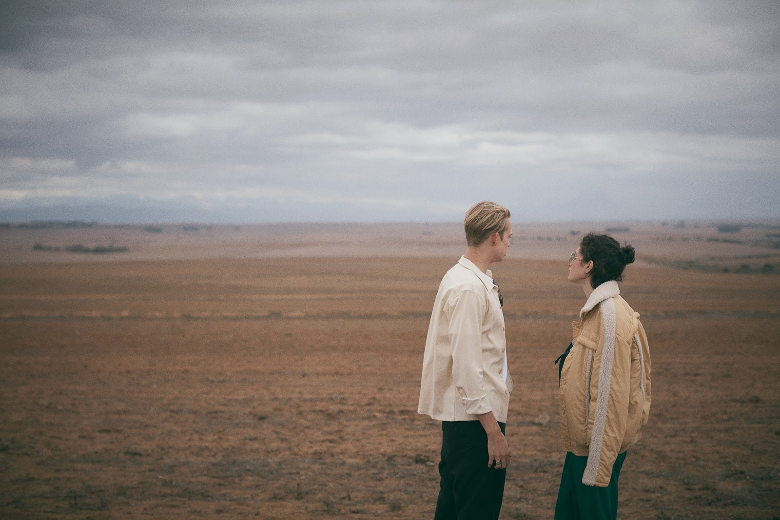 a man and a woman look out across a barren field